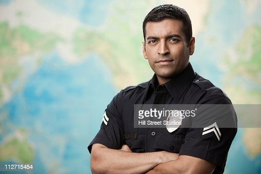 Serious Hispanic policeman with arms crossed : Stock Photo