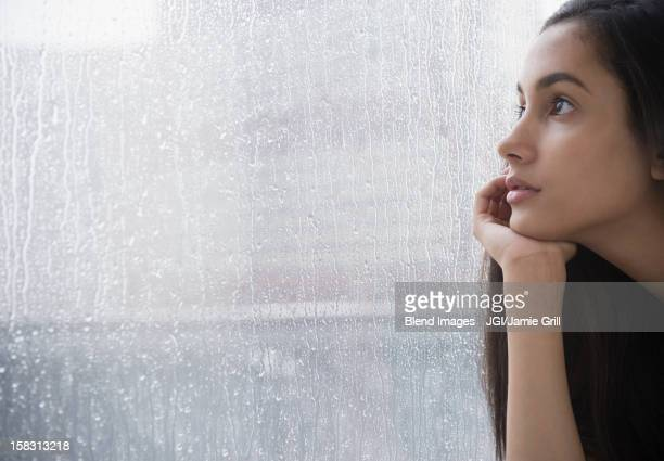 Serious Hispanic teenager looking out window