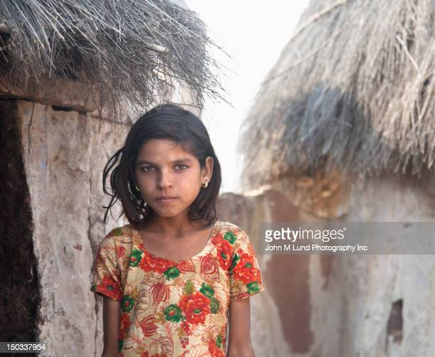 Serious Indian girl near thatched hut, Rajasthan India