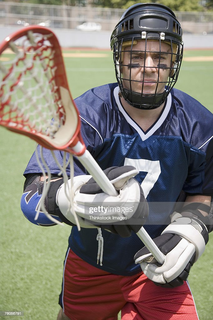 Serious lacrosse player holding crosse