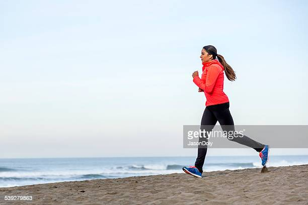 Serious Latino Woman Running on Beach