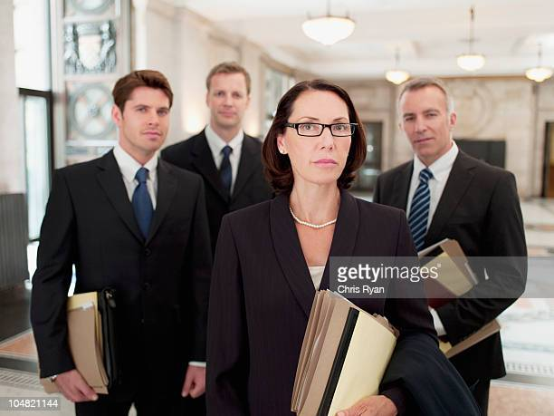 Serious lawyers holding files in lobby