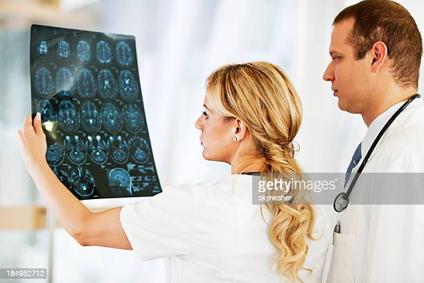Serious looking doctors examining an MRI scan.