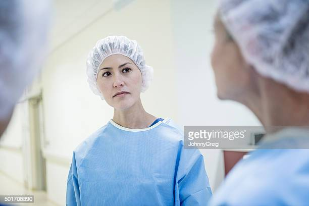 Serious looking female surgeon wearing surgical cap
