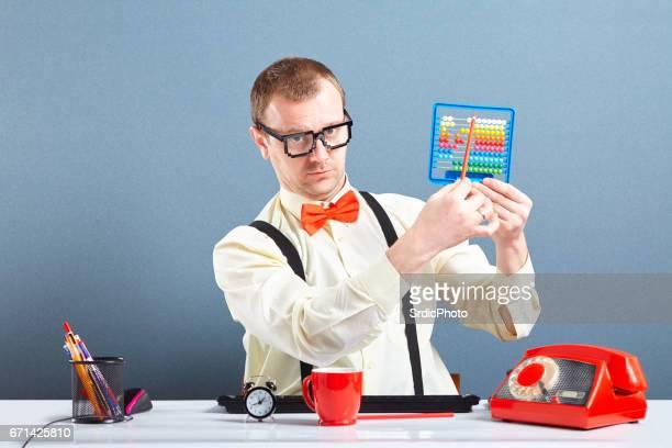 Serious looking nerd guy using abacus