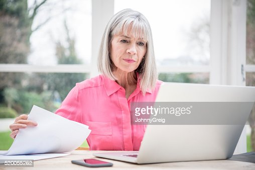 Serious looking senior woman with laptop and paperwork