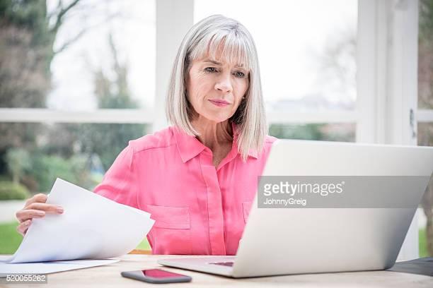 Sérieux regardant Senior Femme avec ordinateur portable et documents