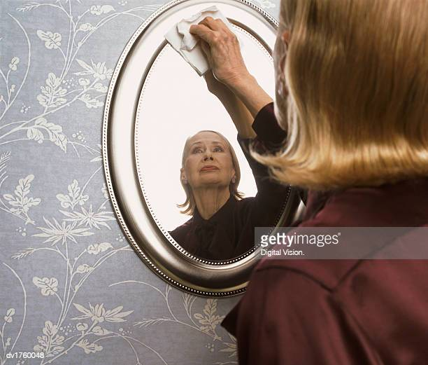 Serious Looking Woman Cleaning a Mirror
