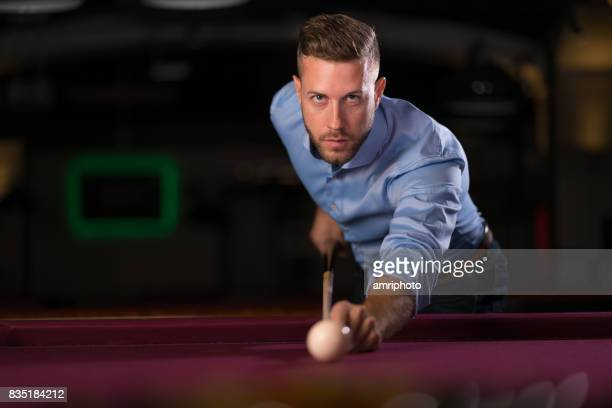 serious looking young man playing pool