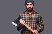 Confident young bearded man holding a big axe and looking at camera while standing against grey background