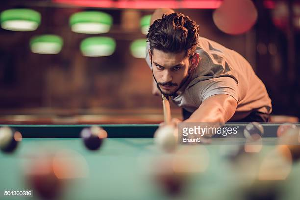 Serious man aiming at pool ball during billiard game.