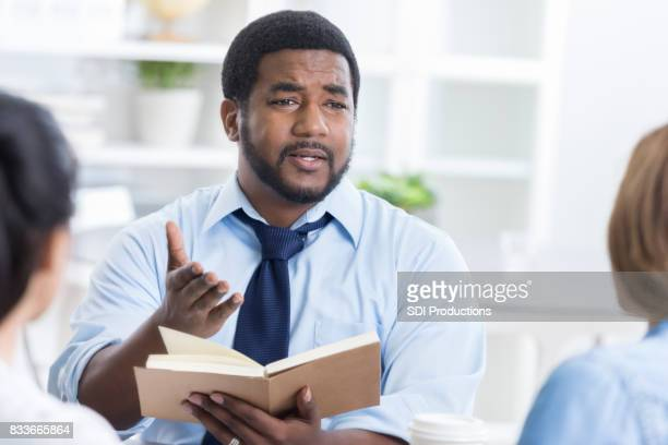 Serious man leads Bible study at work