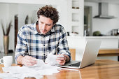 Serious man paying bills online at home
