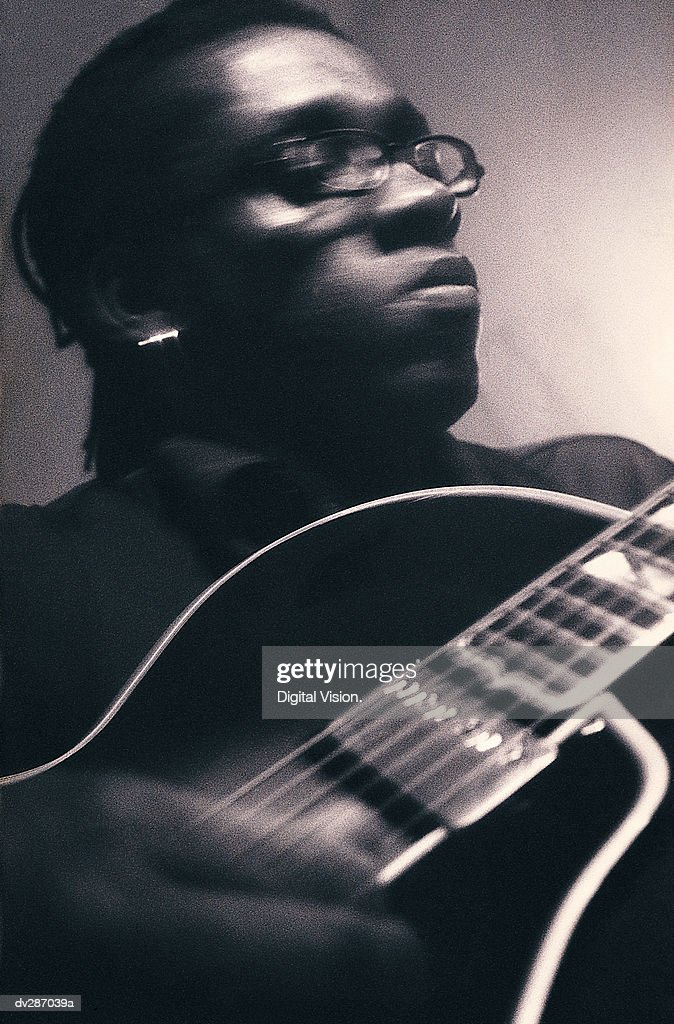Serious man playing guitar : Stock Photo