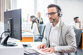 Serious man wearing formal clothes and headset looking at computer screen in bright office