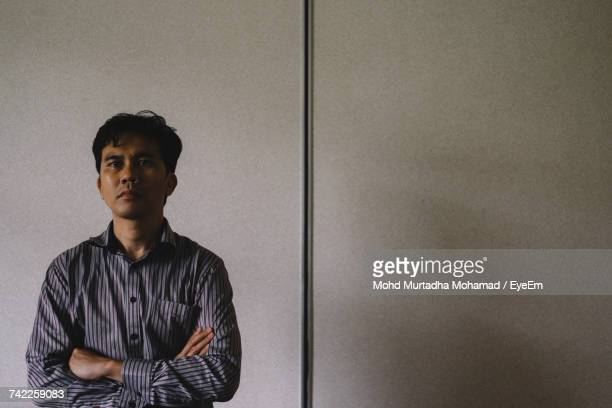 Serious Man With Arms Crossed Standing By Wall