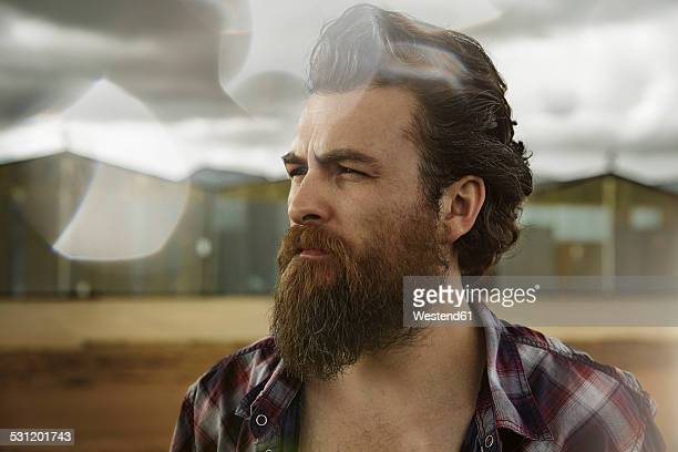 Serious man with full beard in abandoned landscape
