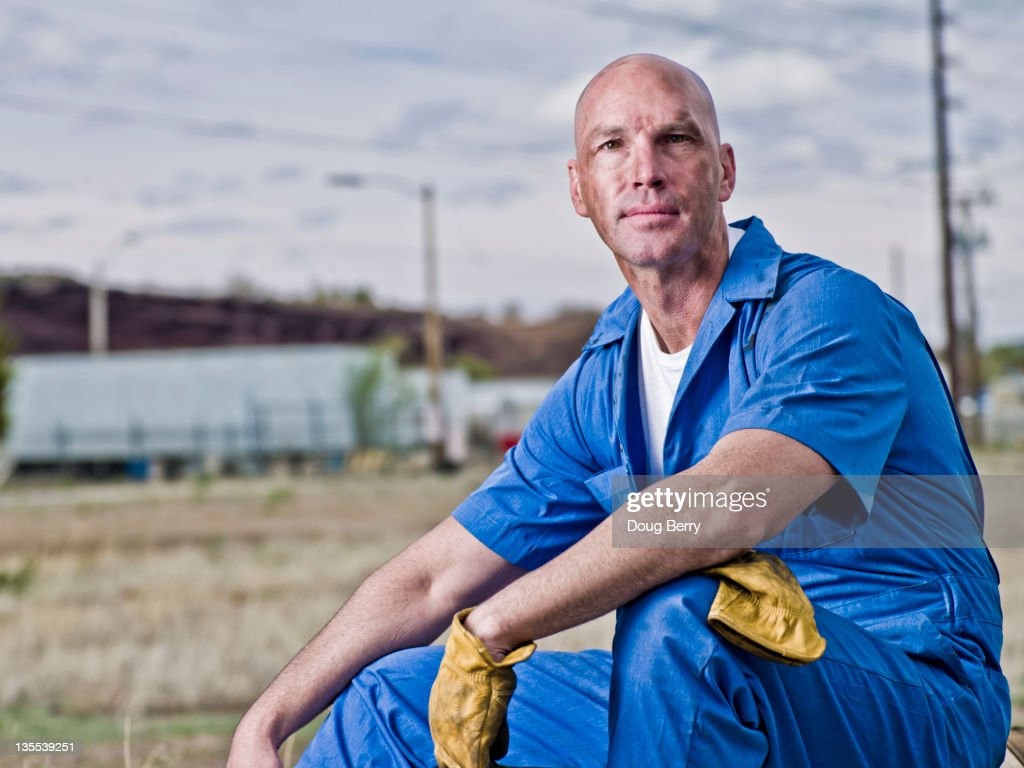 Serious mechanic in coveralls relaxing