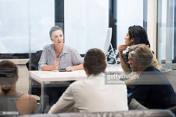 Serious mid adult woman in business meeting explainign to colleagues