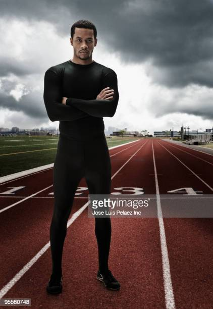 Serious mixed race athlete with arms crossed on running track