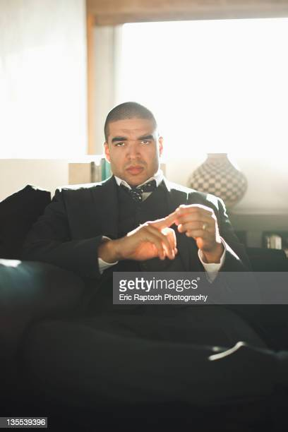 Serious mixed race businessman sitting in chair