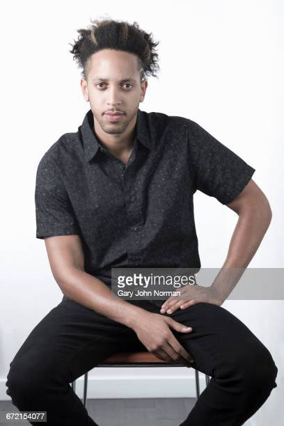 Serious Mixed Race man sitting on chair