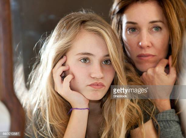 Serious mother and daughter examining themselves in mirror