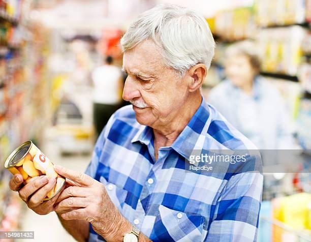 Homem sério Estudos de rótulo de alimentos no supermercado