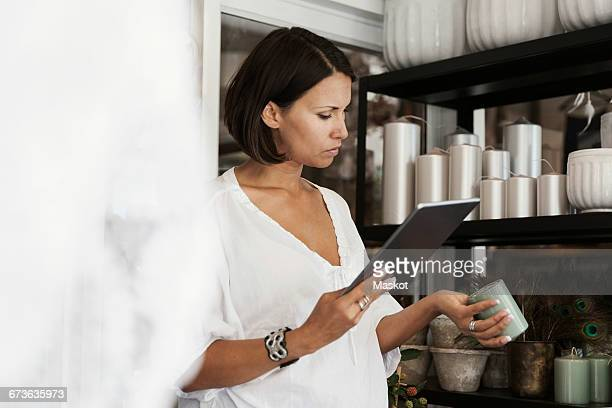 Serious owner checking candle while using digital tablet at store