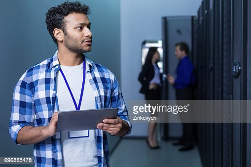 Serious pleasant man working on a tablet : Stock Photo