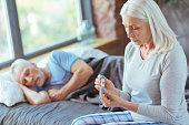 Concerned about health. Sad aged woman holding a thermometer and sitting on bed while her sick husband sleeping in the background