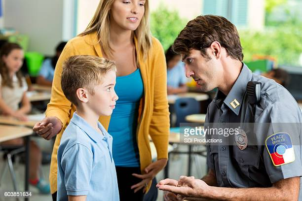 Serious security officer talks with elementary student at school