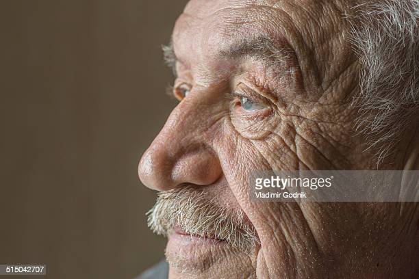 Serious senior man looking away isolated over colored background