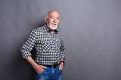 Serious senior man posing with hands on hips, gray studio background, copy space