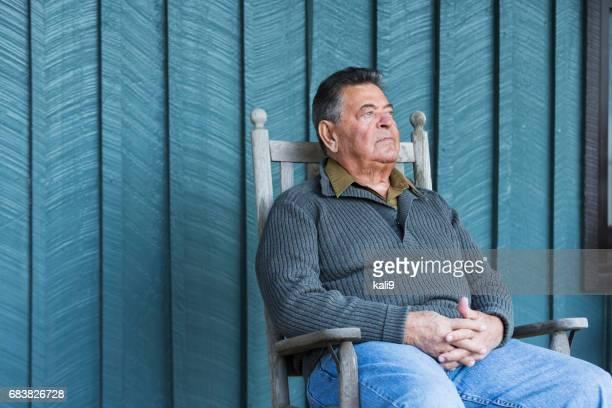 Serious senior man sitting in rocking chair on porch