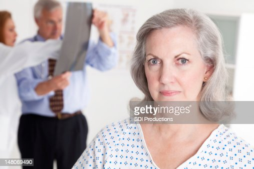 Serious Senior Patient in Doctor Office While Physicians Examine X-Ray : Stock Photo