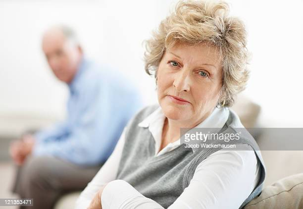 Serious senior woman sitting with a man in background