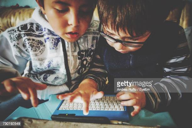 Serious Siblings Using Technology At Home