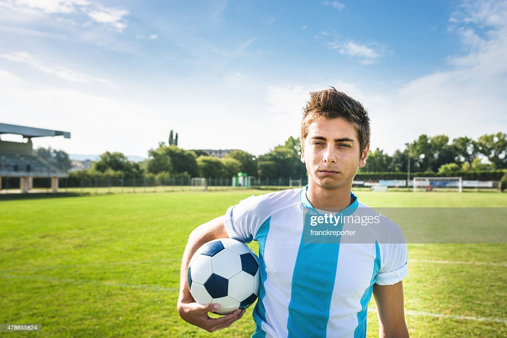 Serious soccer player portrait on the pitch