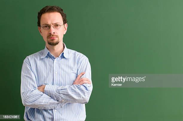 serious teacher with arms crossed at blackboard