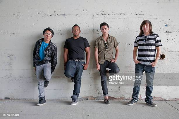 Serious teenage boys leaning against wall