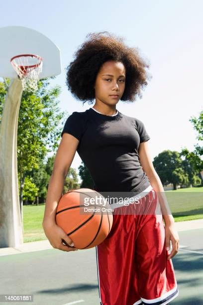 Serious teenage girl holding basketball on court