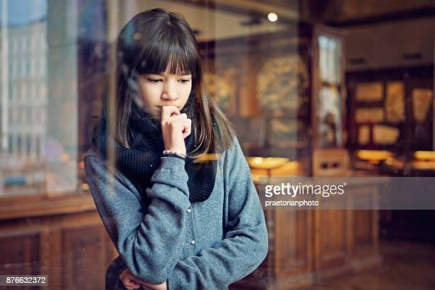 Serious teenage girl is looking museum exhibition with interest
