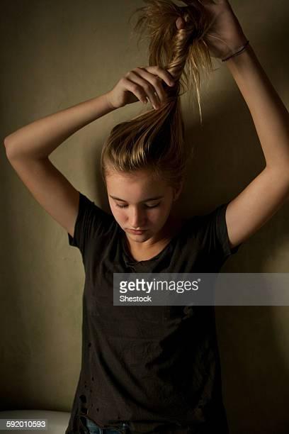 Serious teenage girl twisting her hair
