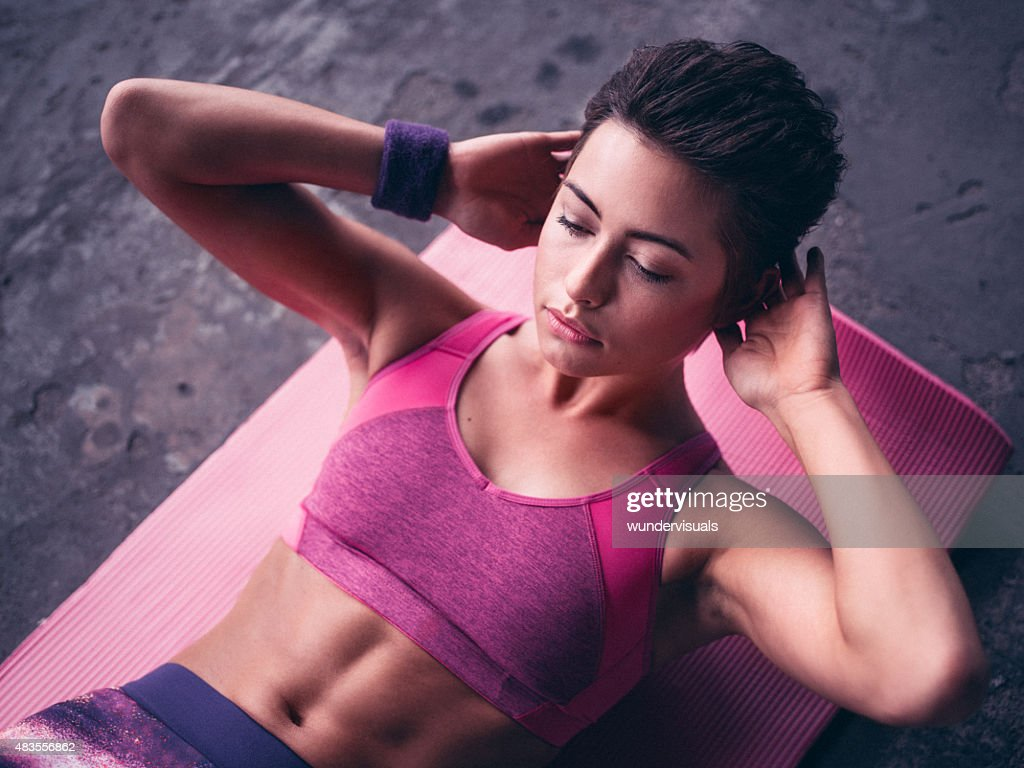 Serious woman doing sit ups on a pink exercise mat : Stock Photo
