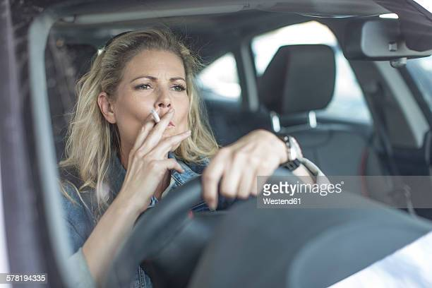 Serious woman in car smoking a cigarette