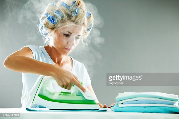 Serious woman ironing her clothes.