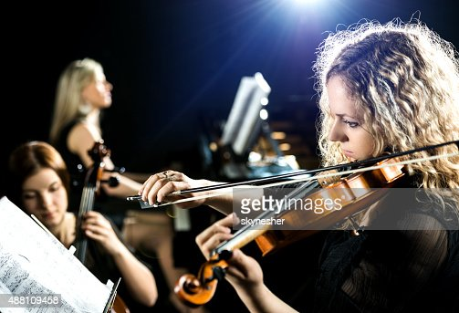 Serious woman playing the violin.