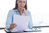 Serious woman reading and examining document. Entrepreneur sitting at desk and working. Paperwork and recruitment concept. Front view.
