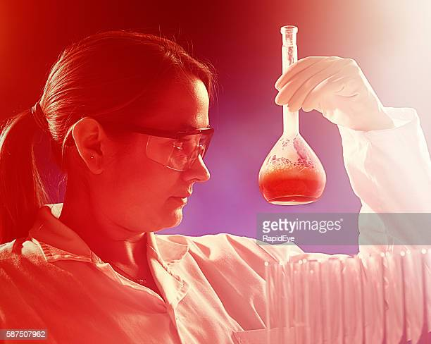 Serious woman scientist studies flask of liquid in red-toned image